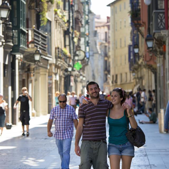"""Young couple stroll arm in arm in Calle de Bidebarrieta in Bilbao, Spain"" stock image"