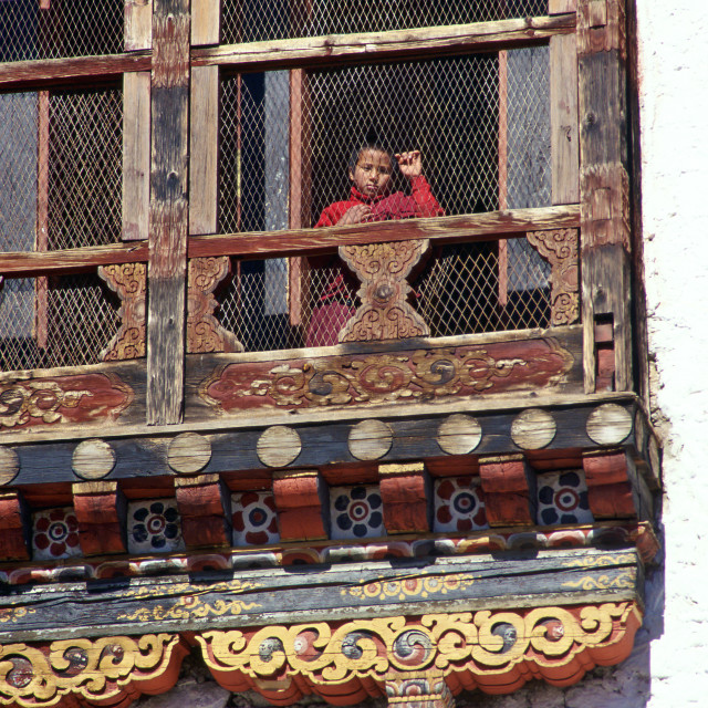 """Child watching from carved decorative window, Thimpu, Bhutan"" stock image"