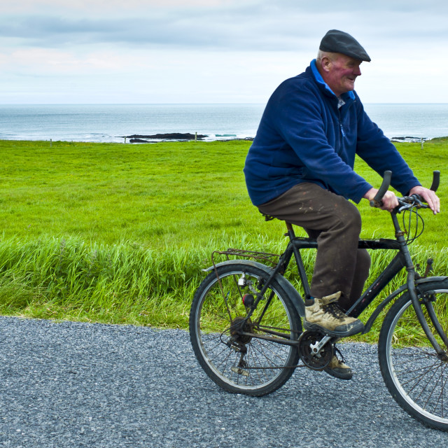 """Local Irish man cycling traditional bicycle along country lane in County..."" stock image"