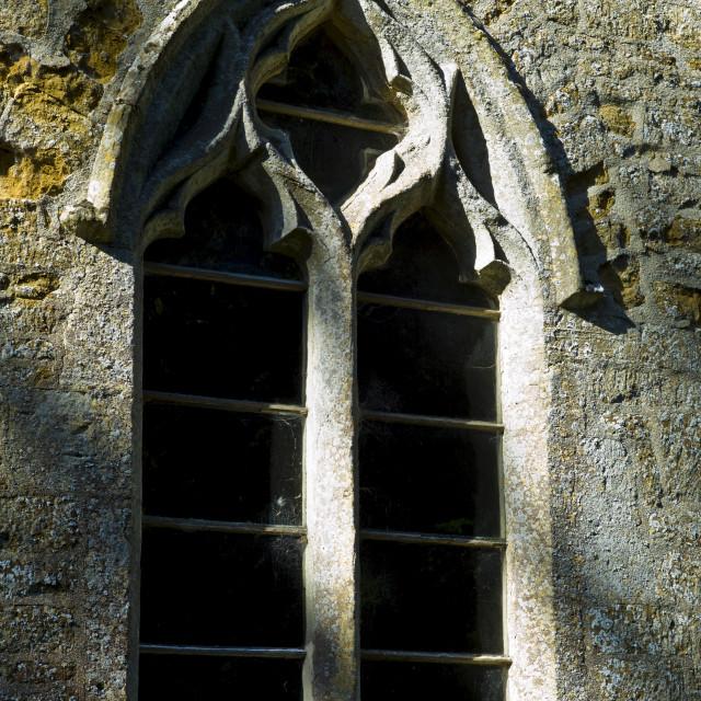 """Norman style old stone window at 11th Century St Nicholas Church, Oddington,..."" stock image"