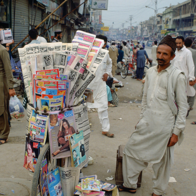 """""""Man selling newspapers stacked on a bicycle in the streets of Islamabad in..."""" stock image"""