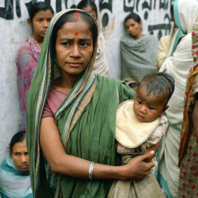 """A mother carrying her child and queuing for food handouts withother women at..."" stock image"