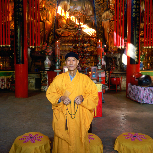 """""""A Buddhist monk in saffron coloured robes praying in front of a statue of..."""" stock image"""