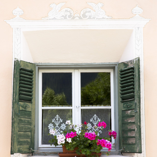 """Window in old painted stone 17th century building in the Engadine Valley in..."" stock image"