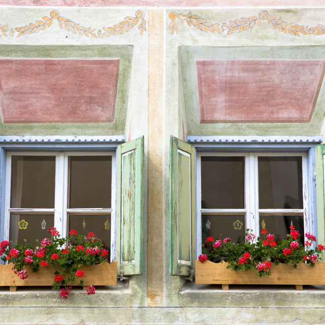 """Windows in old painted stone 17th century building in the Engadine Valley in..."" stock image"