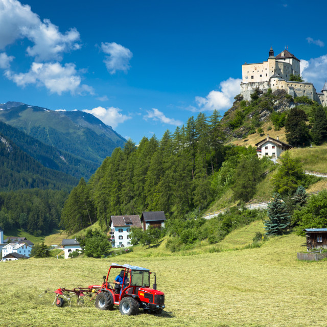 """Farmer turning hay at Tarasp in the Lower Engadine Valley, Switzerland, Europe"" stock image"