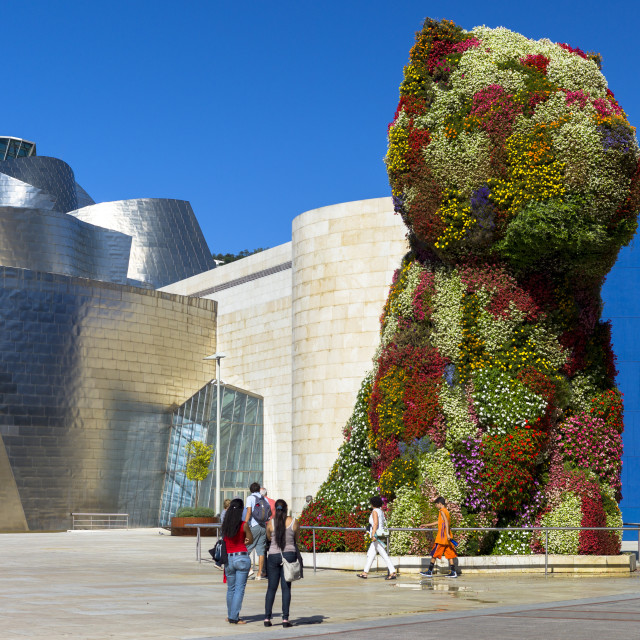 """""""Tourists view Puppy flower feature floral art by Jeff Koons at Guggenheim..."""" stock image"""