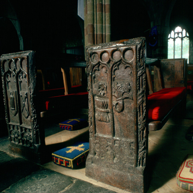 """Ornate, ancient wooden carved pews and tapestry kneeling pads in St. Keverne..."" stock image"