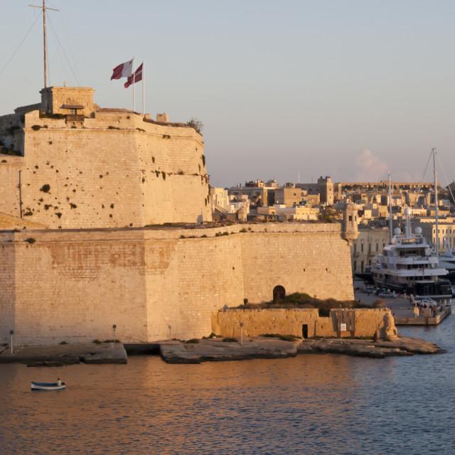 """Fort St. Angelo, fishing boat and Vittoriosa (Birgu) at sunset, Grand..."" stock image"