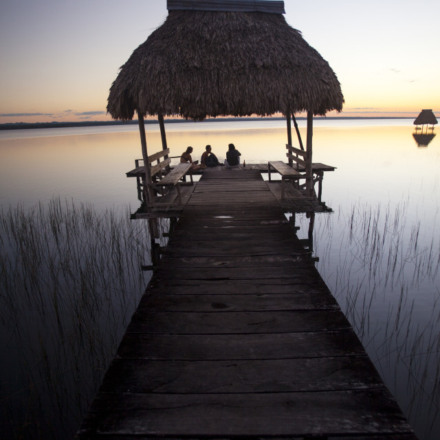 """""""People relaxing at sunset, Lago Peten Itza, El Remate, Guatemala, Central..."""" stock image"""