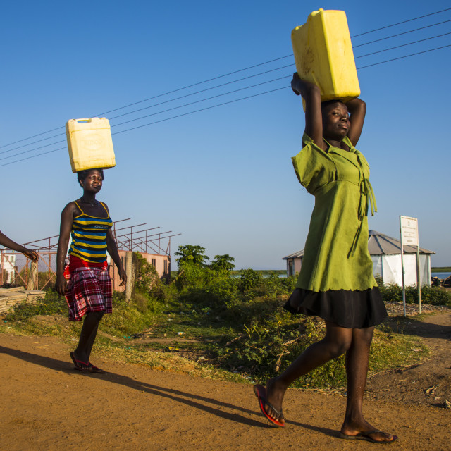 """Women carrying water canisters on their head bringing water home from Lake..."" stock image"