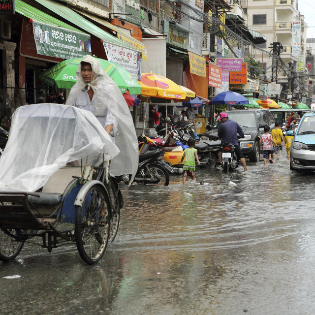 """""""Traffice, including a cyclo and taxi, on a waterlogged street during the..."""" stock image"""