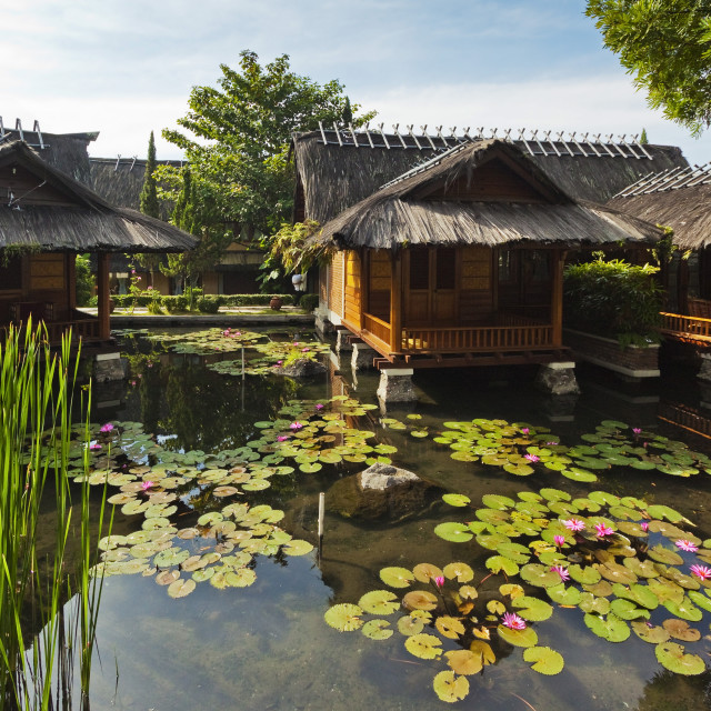 """Traditional kampung style rooms over carp ponds at the Kampung Sumber Alam..."" stock image"