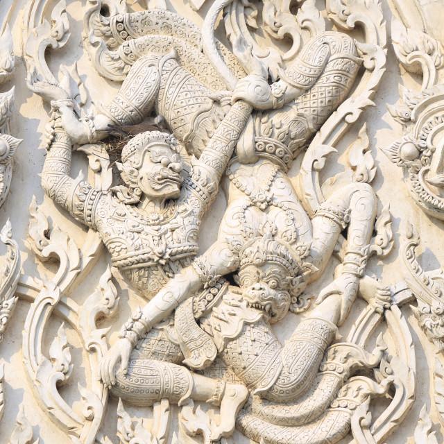 """Detail of battling demons on Khmer style Wat Mahathat Worawihan temple in..."" stock image"