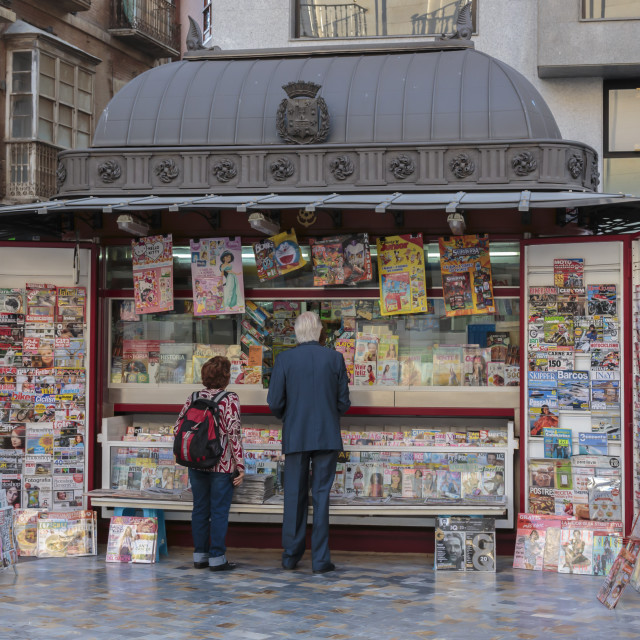 """""""People stand at a red newspaper and magazine kiosk with fancy roof,..."""" stock image"""