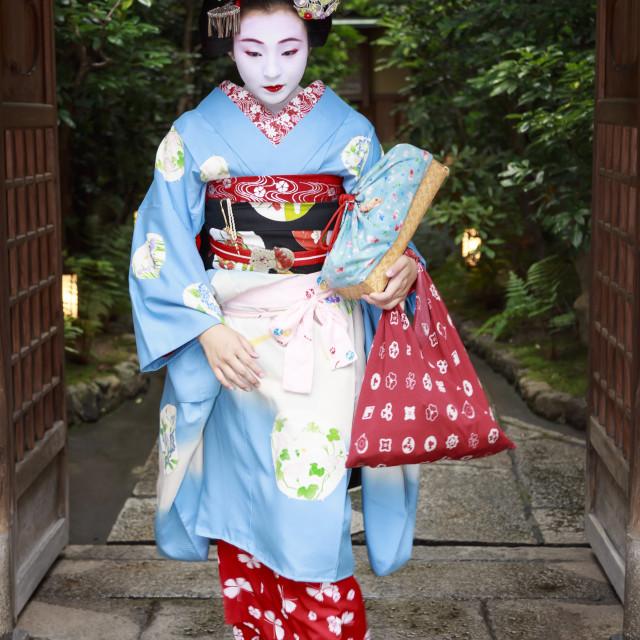 """Maiko, apprentice geisha, leaves okiya (geisha house) through garden gate for..."" stock image"