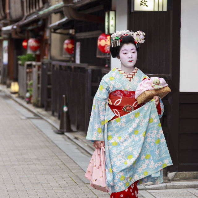 """Maiko apprentice geisha, in street of traditional wooden buildings, walks to..."" stock image"