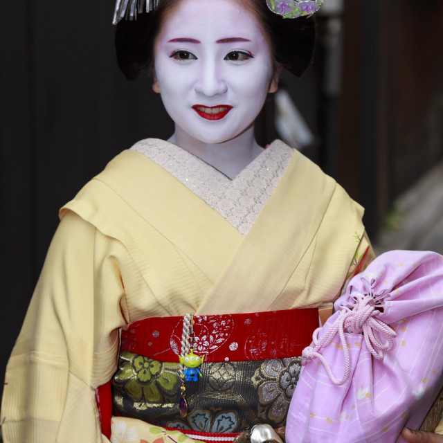 """Smiling maiko, apprentice geisha, with yellow robes, stops in street on way..."" stock image"