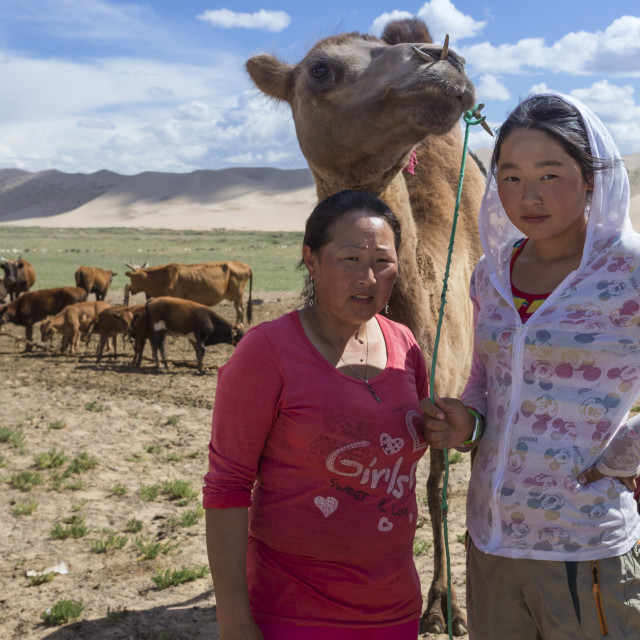 """""""Nomadic camel herders, mother and daughter, with two hump Bactrian camel..."""" stock image"""