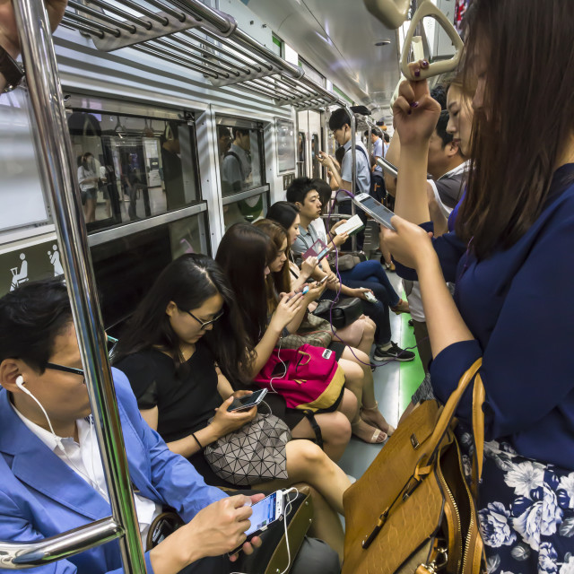 """Smartly dressed commuters on the busy subway looking at their phones and..."" stock image"