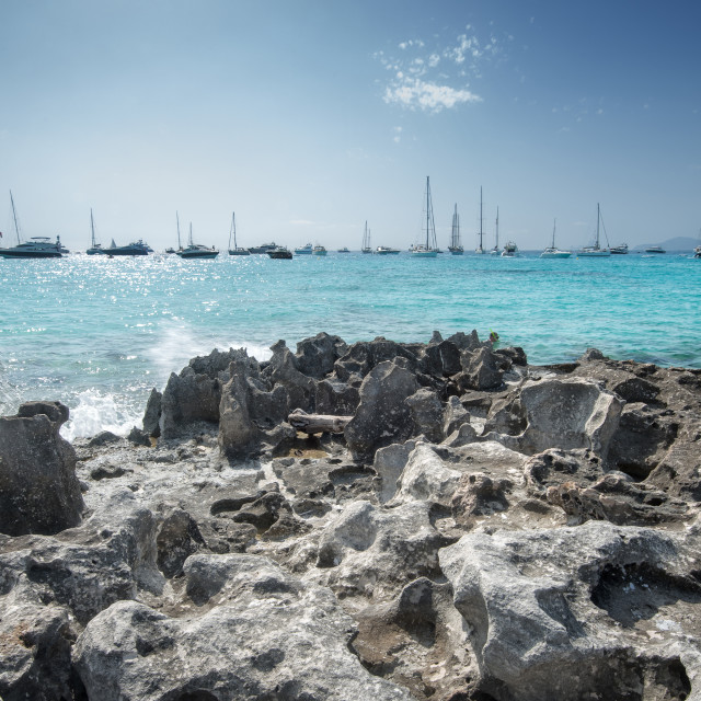 """Jagged rocks with sailboats idling in the azure waters of Formentera."" stock image"