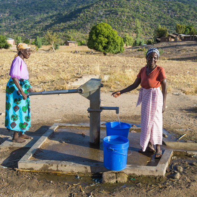 """Women pumping water out of a well at Lake Malawi, Cape Maclear, Malawi, Africa"" stock image"