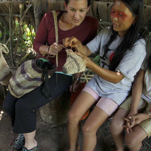 """Western tourists at an eco-tourism journey learn local crafts from Huaorani..."" stock image"