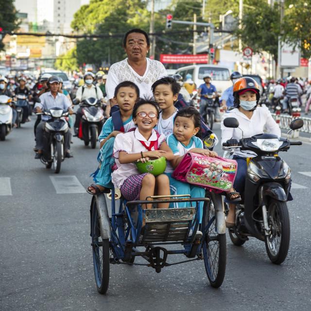 """School kids riding a cyclo on a busy street, Ho Chi Minh City (Saigon),..."" stock image"