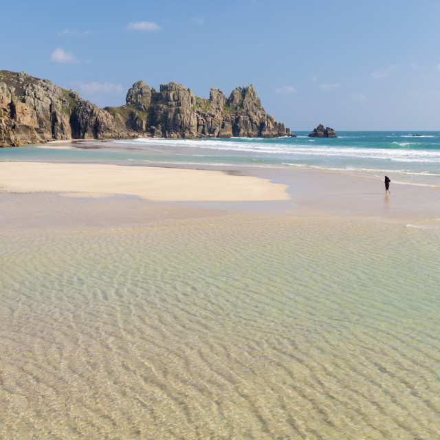 """Woman walking alone on Pednvounder Beach at low tide, Porthcurno, Cornwall,..."" stock image"