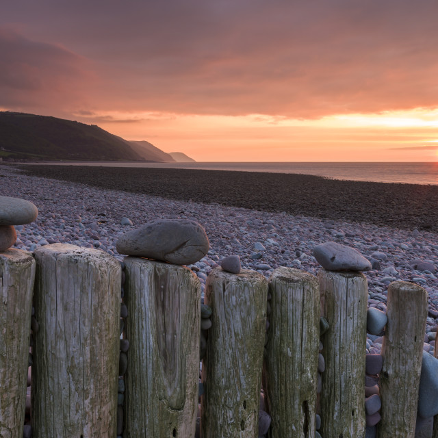 """""""Pebbles on wooden posts at sunset, Bossington Beach, Exmoor National Park,..."""" stock image"""