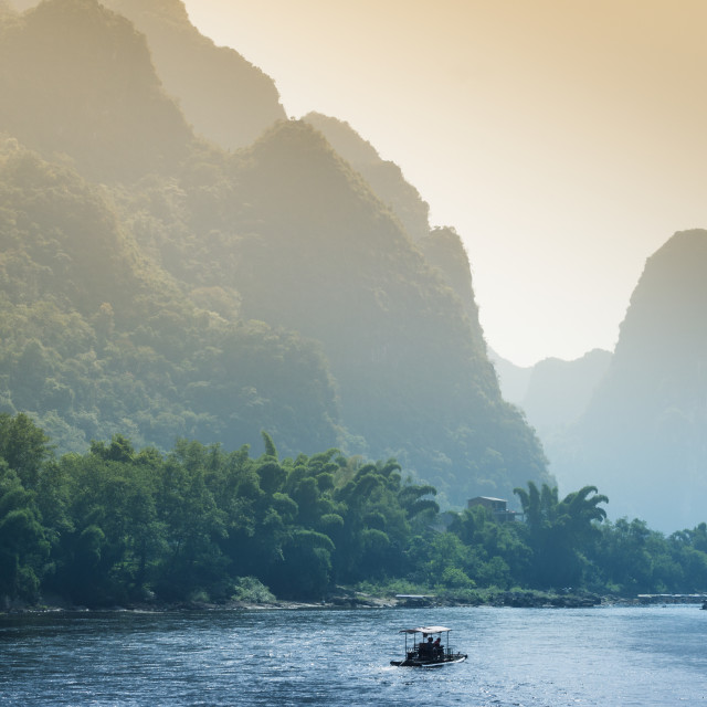 """Picturesque countryside scenery along Li River with small boat in water..."" stock image"