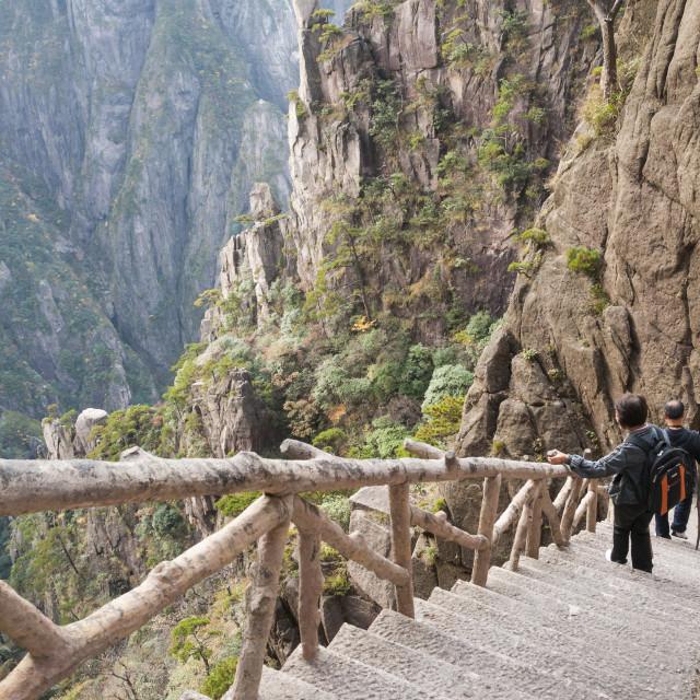 """""""Mature Asian couple descend concrete steps built into rock face on the Xihai..."""" stock image"""