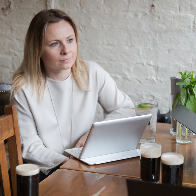 """""""Young businesswoman sitting at wooden table in bar having a tabl"""" stock image"""