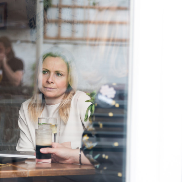 """Pensive blonde attractive young adult single woman in pub"" stock image"