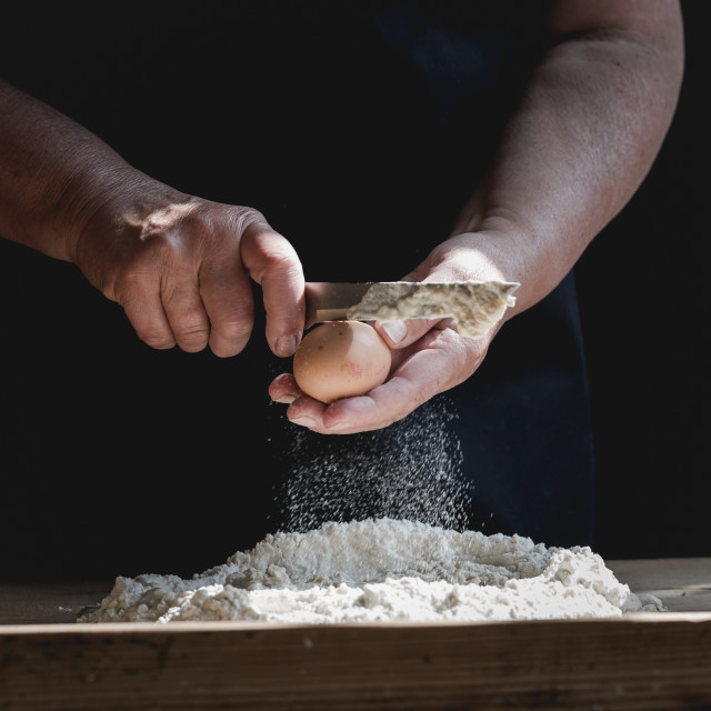 """Senior woman smashes an egg using knife while kneading a pastry"" stock image"