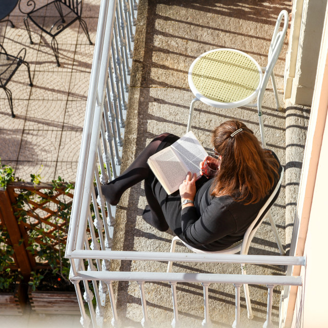 """A woman relaxing on holiday on a hotel balcony reading a book an"" stock image"