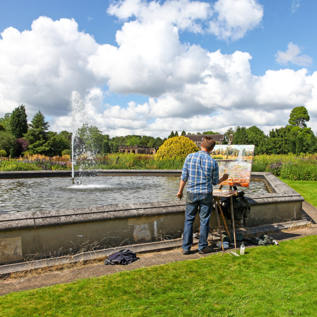 """A man painting a fountaion outside in summer at Trentham Gardens"" stock image"