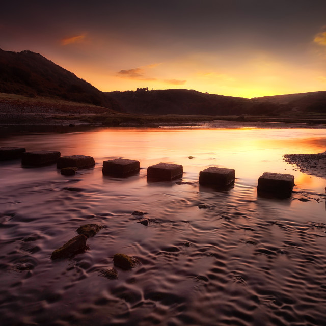 """Sunrise at Three Cliffs Bay"" stock image"