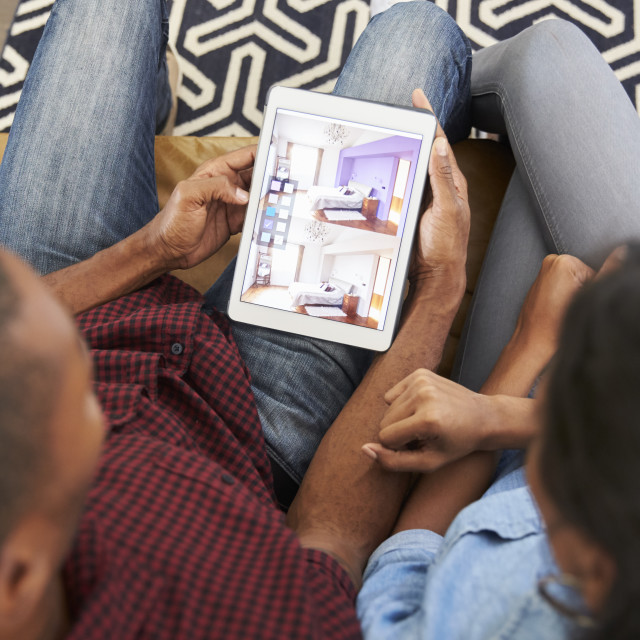 """Couple Sitting On Sofa Looking At Home Improvement App"" stock image"