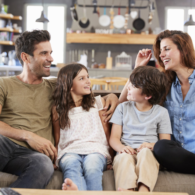 """""""Happy Family Sitting On Sofa In Lounge Talking Together"""" stock image"""