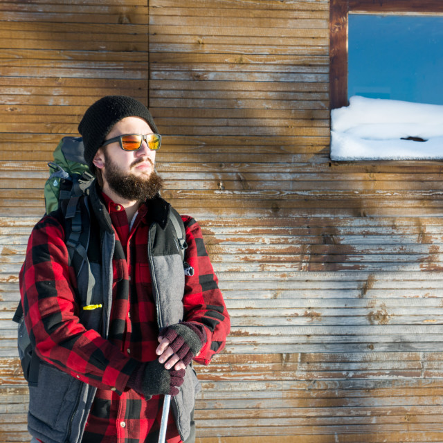 """Bearded hiker in front of log cabin"" stock image"