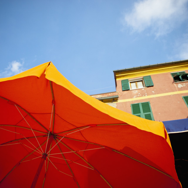"""Yellow And Bbue Patio Umbrellas Below A Building; Vernazza, Liguria, Italy"" stock image"