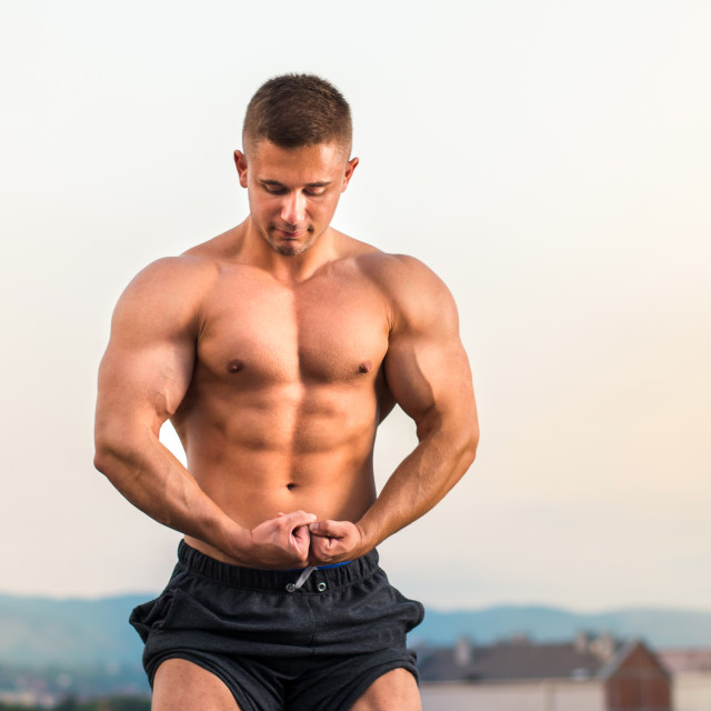 """""""Bodybuilder flexing muscles on a rooftop"""" stock image"""