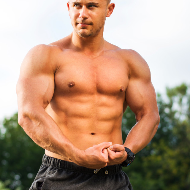 """""""Young bodybuilder flexing muscles outdoors"""" stock image"""