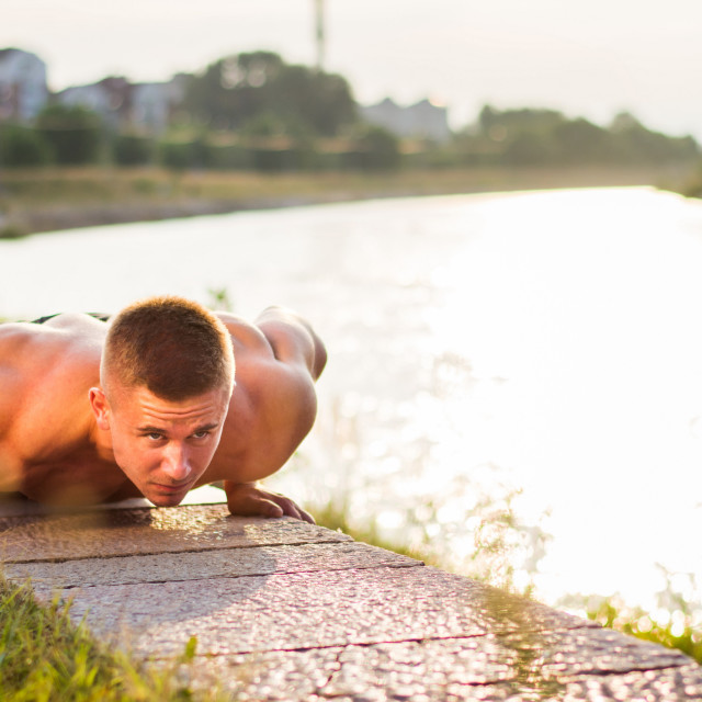 """""""Man performing push ups by the river"""" stock image"""