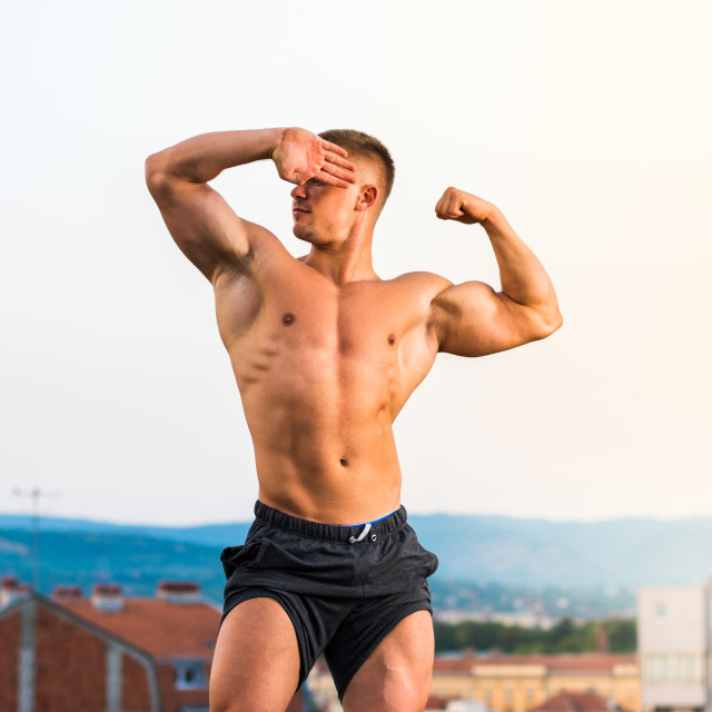 """""""Man flexing muscles on a rooftop"""" stock image"""