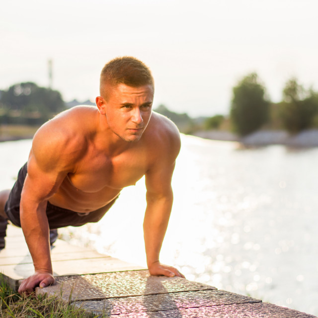 """""""Man doing push ups by the river"""" stock image"""