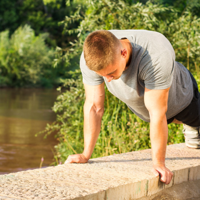 """Man doing push ups by the river"" stock image"