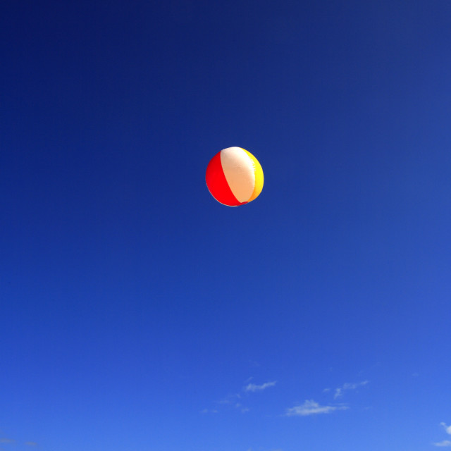 """Colorful Beachball Flying Through Bright Blue Sky."" stock image"