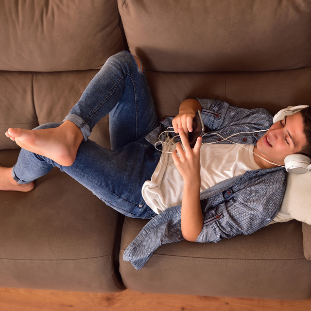 """""""Teen lying face up on couch consuming multimedia content top"""" stock image"""